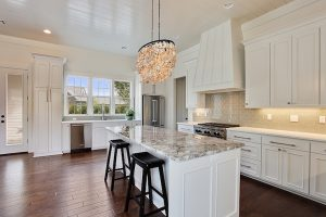 seashell-chandelier-white-kitchen-cabinets-gray-granite-countertops